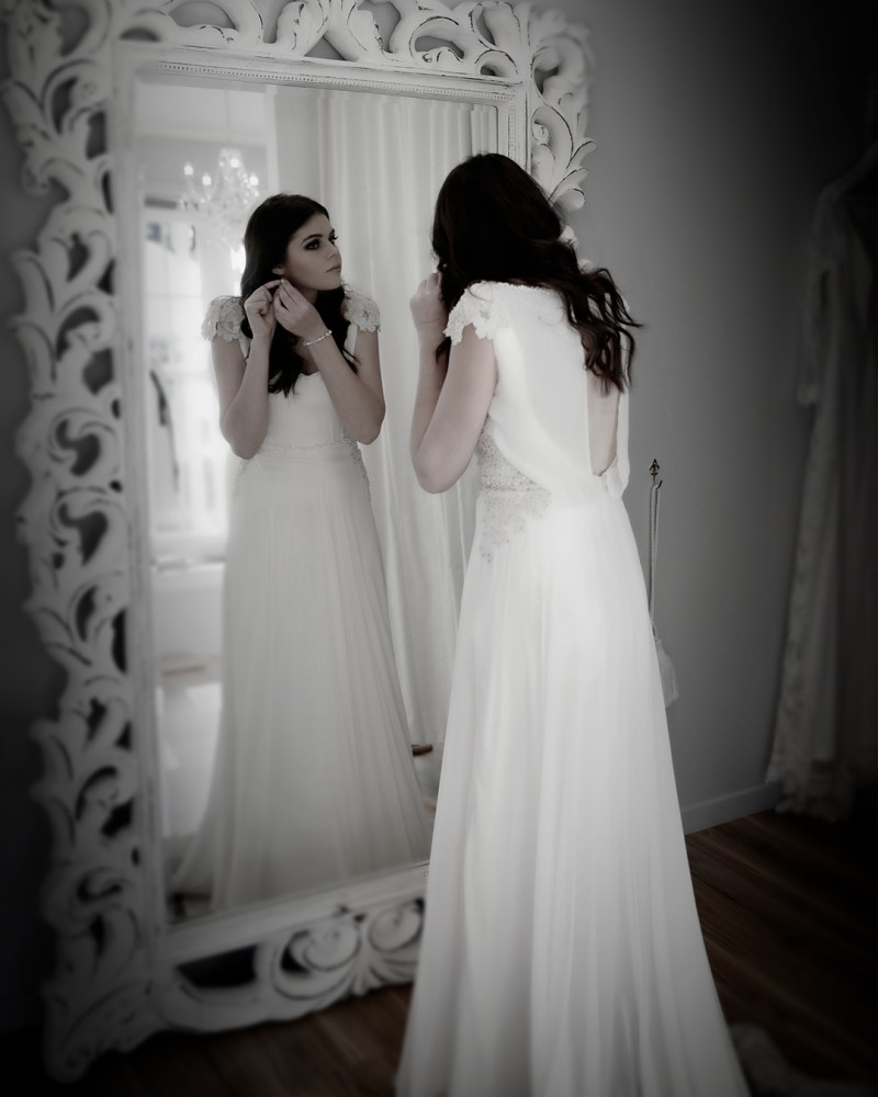 A woman in a white wedding gown stands in front of a mirror in a bridal gown boutique
