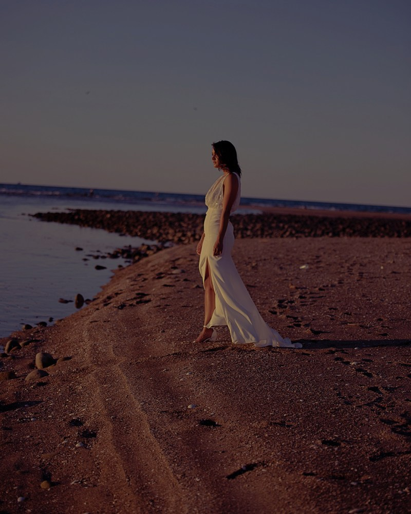 A woman in a white wedding gown stands on a beach in the Bay of Plenty