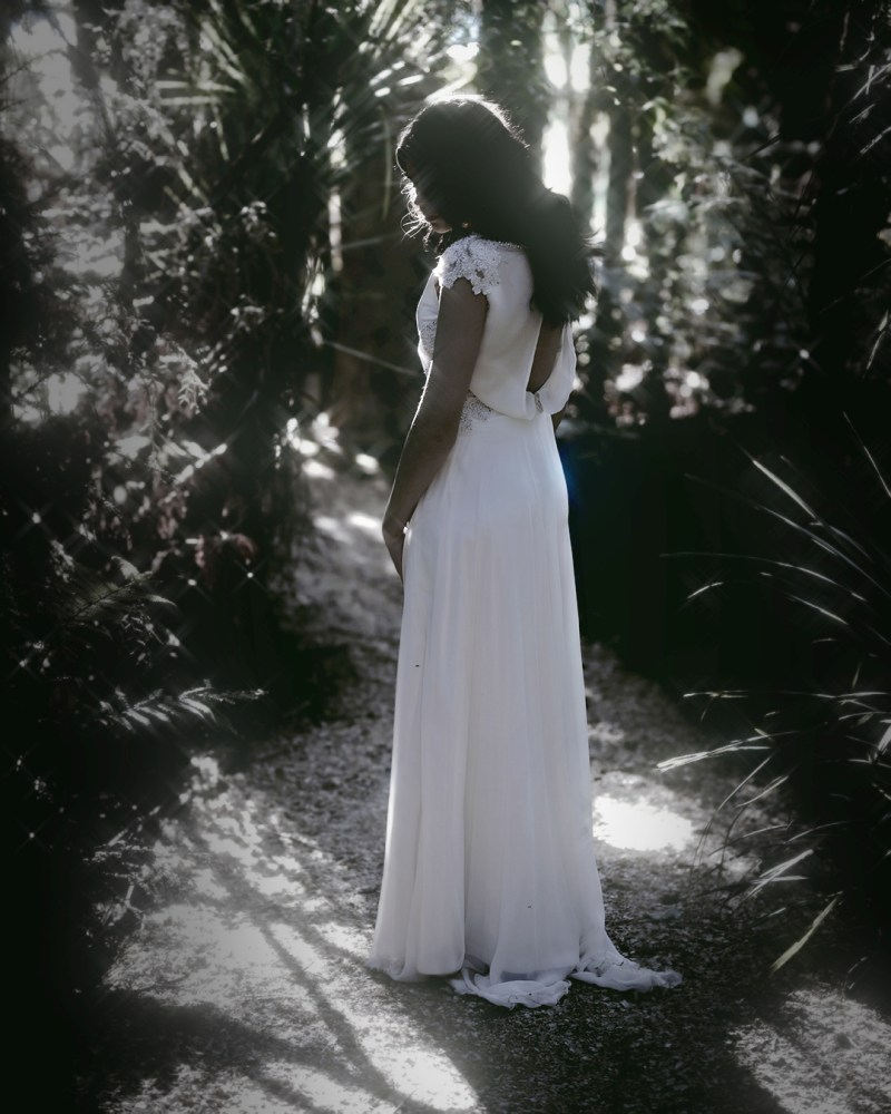 A woman in a white bridal gown stands in a clearing in Tauranga