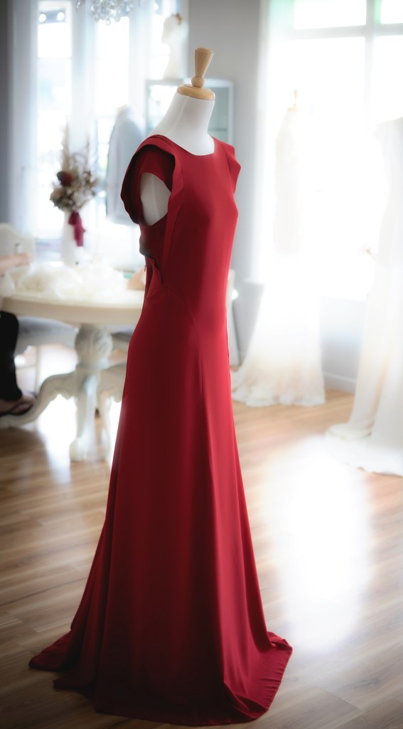 A red ball gown sits on a designer's gown mannequin in a boutique