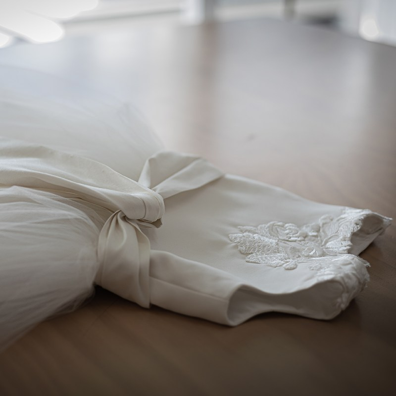A christening gown lays flat on a table in a boutique