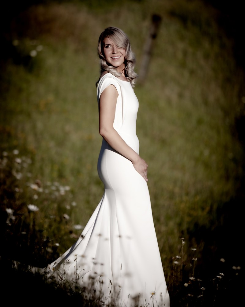 A woman with blonde hair stands in a field wearing a white bridal gown