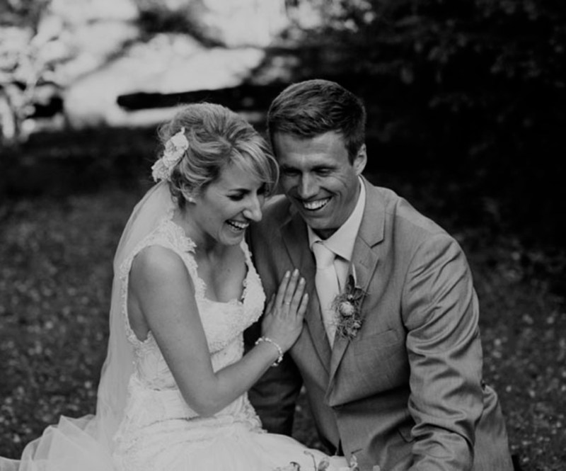A bride and groom both smile with joy as they sit on grass after their wedding