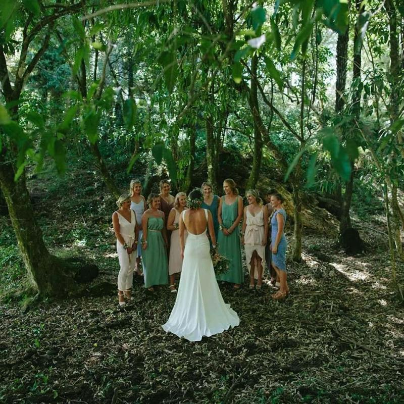 A bride in a wedding dress stands with her bridesmaids in a forest after her wedding