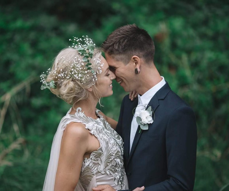 A woman with blonde hair and wearing a bridal gown is held by a groom during a real wedding
