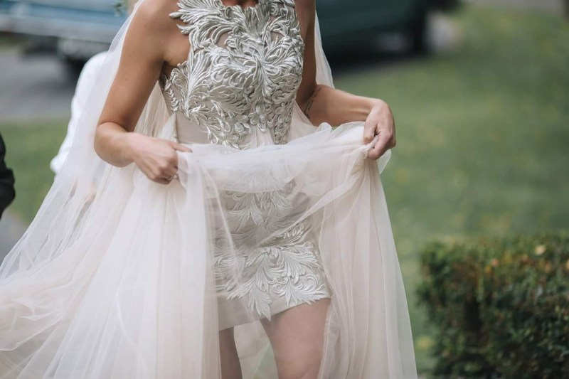 A close up shot of a decorative bridal gown as the bride raises her train following a wedding