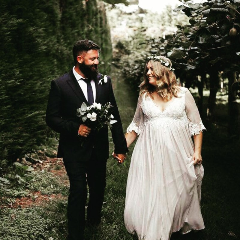 A groom in a suit holds his wife's hand as they walk next to trees after their wedding
