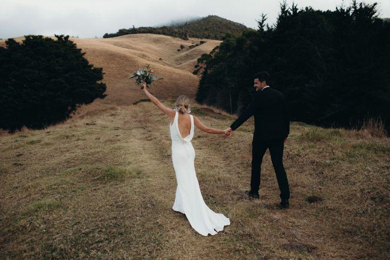 A bridal couple walk on a hill