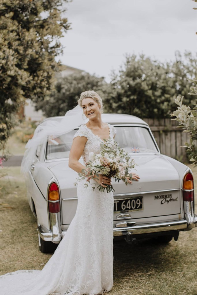 A woman in a bridal gown smiles as she stands in front of a vintage car