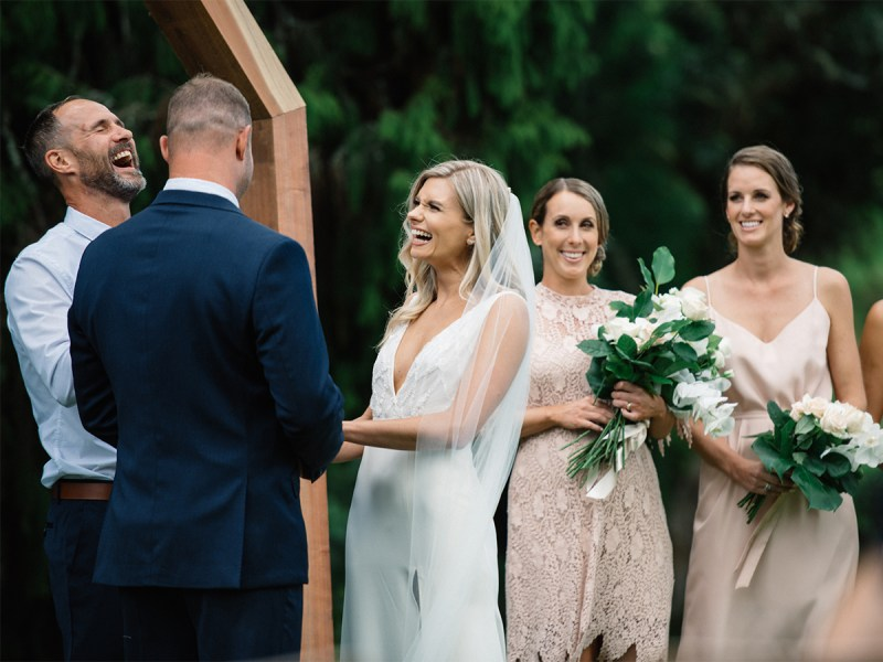 A woman in a bridal gown smiles as she stands opposite her groom in an outside wedding
