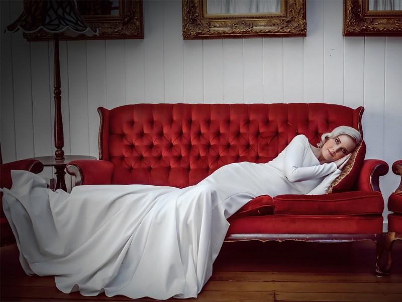 A woman in a white bridal gown lies on a red sofa in a room with many mirrors