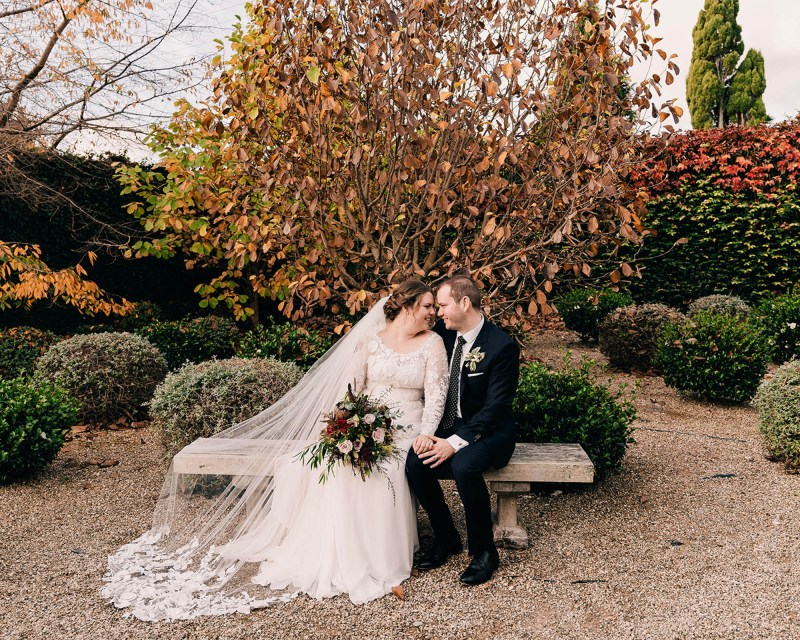 A bride in her wedding dress sits outside with her groom