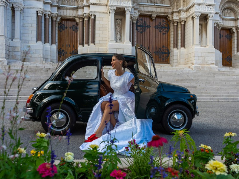 A woman in a wedding dress smiles as she leans out of a small black car parked in front of steps
