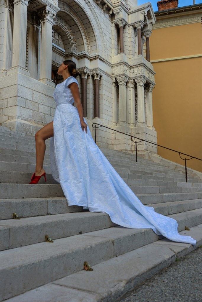 A young woman stands on steps whilst wearing a white bridal gown