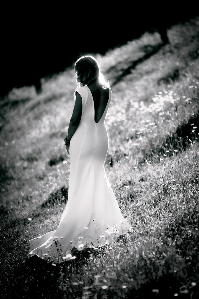 A woman wearing a white bridal gown in a field, with her back turned