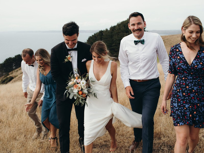 A couple just married walk with a bridal party across a field
