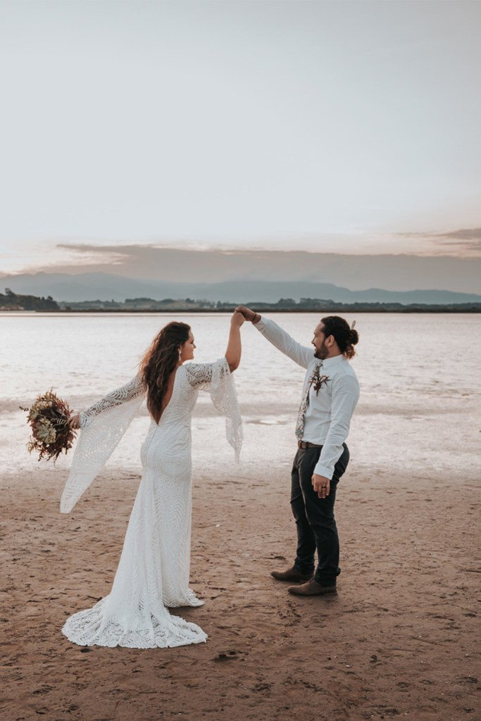 A bride in a wedding dress dances on a beach with her groom