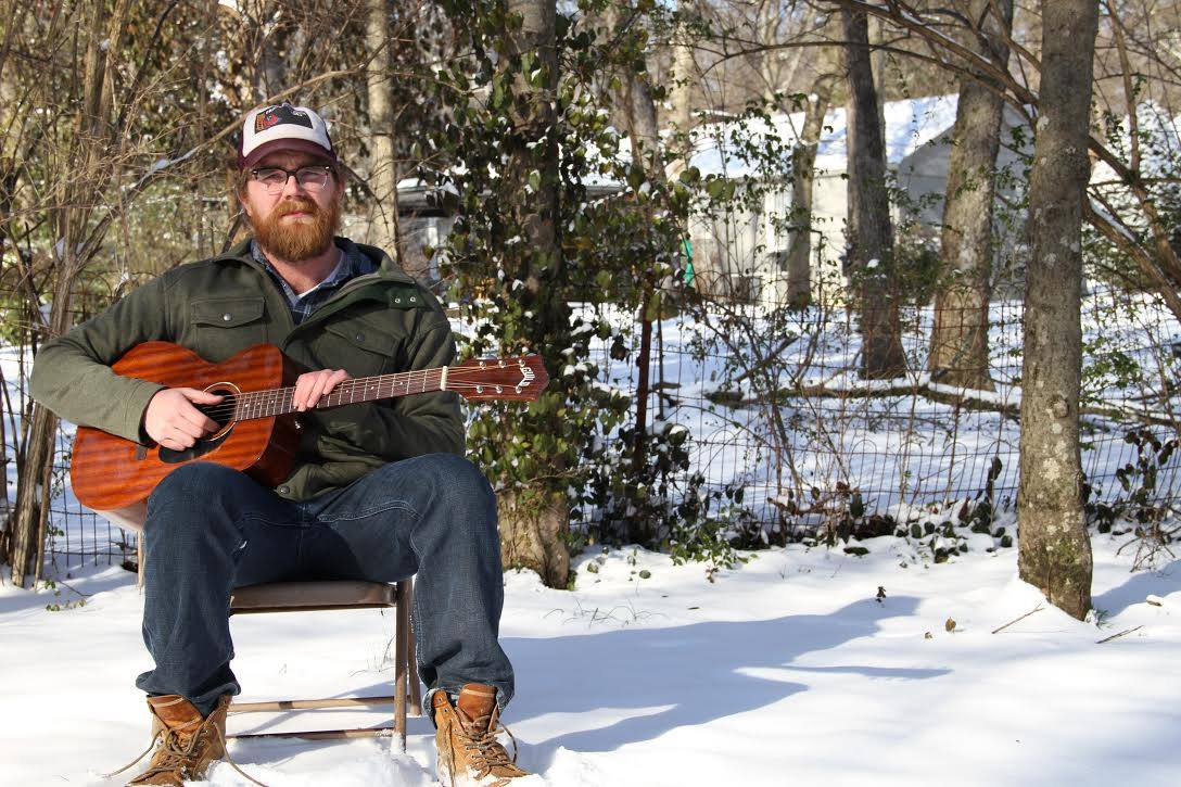 Brian Johannesen sits outside with his acoustic guitar.