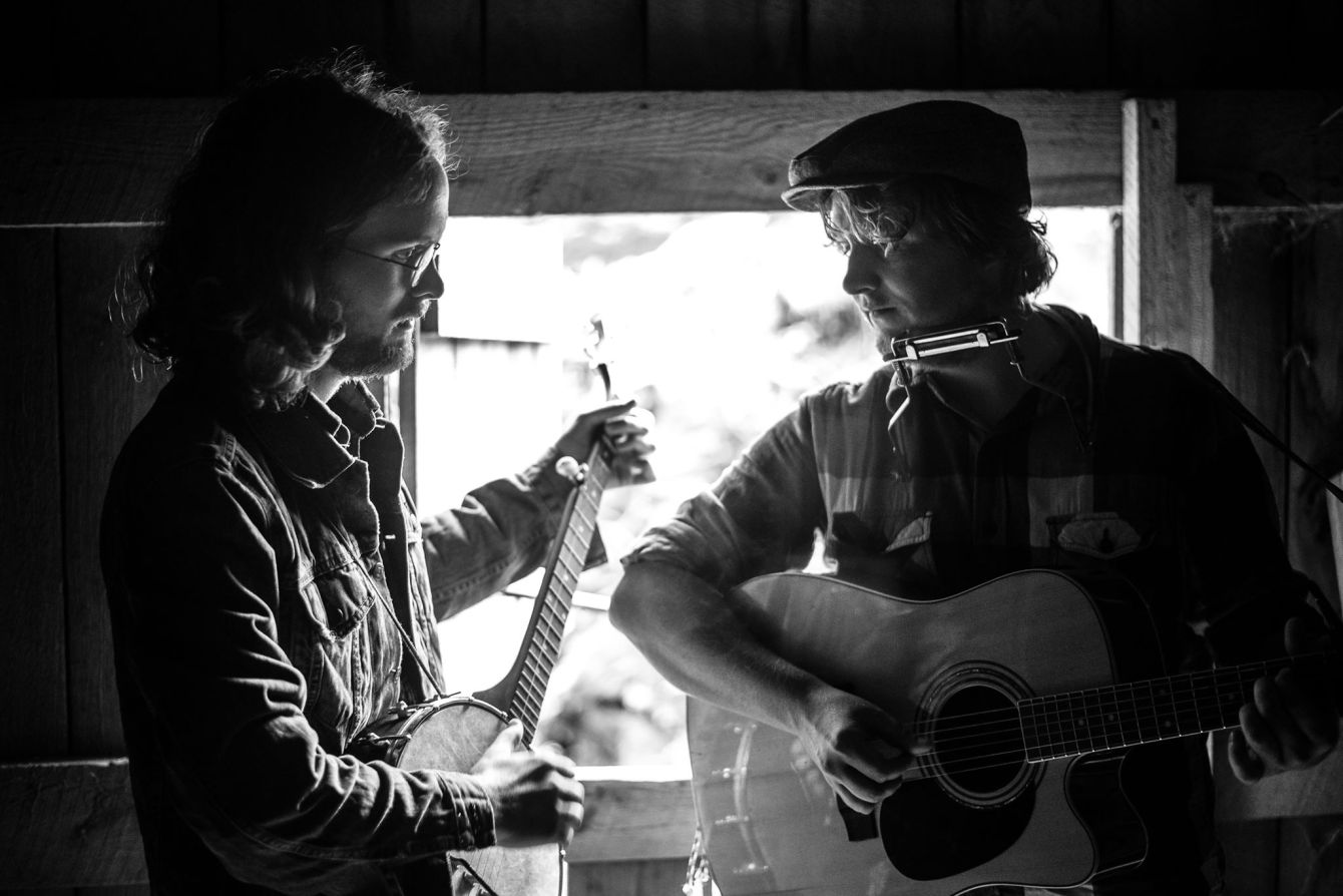 Black and white photo of Tough Old Bird playing a banjo and acoustic guitar