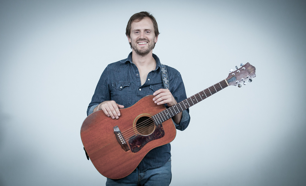 Alaska's Michael Howard smiles with his acoustic guitar at The White Wall in Sioux Falls.