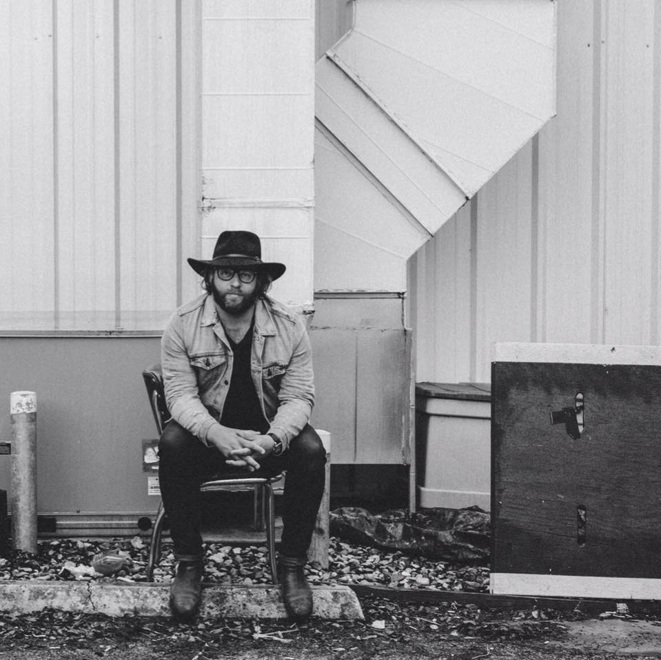 Trap Kit, Andrew Jandt, sits in a cowboy hat in a black & white photo in front of a metal shed