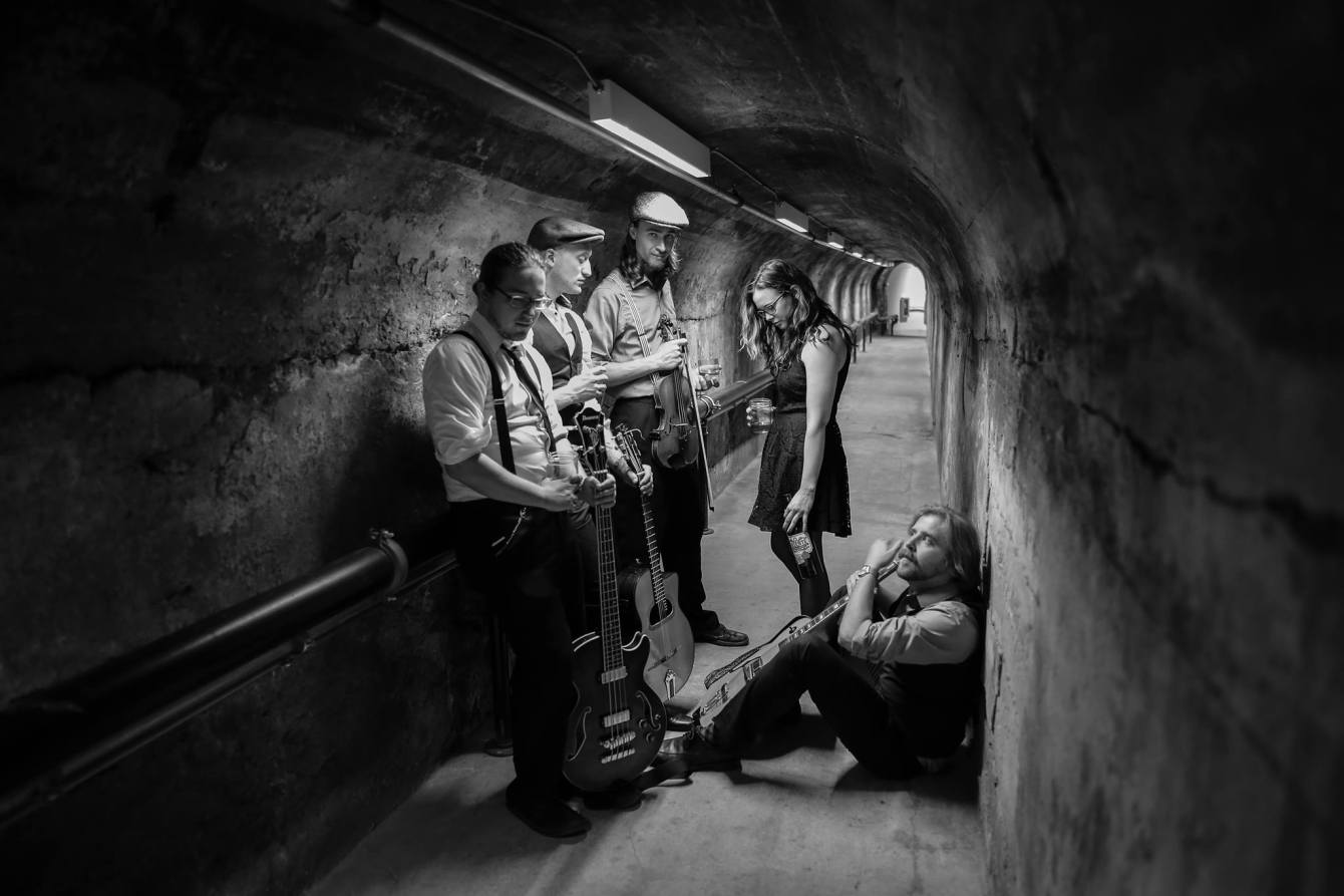 Black and white photo of The Gentlemen's Anti-Temperance League posing in a tunnel