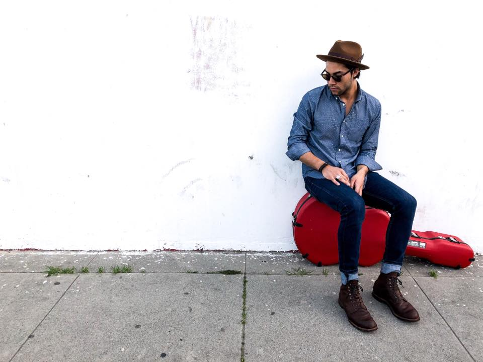 Rascal Martinez sits by a white wall on a red guitar case.