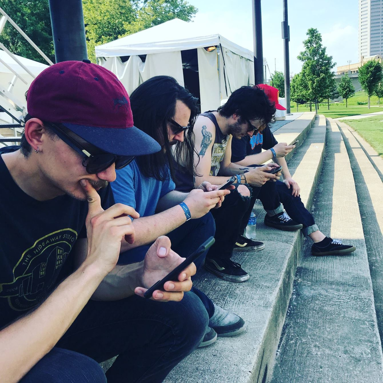 4 members of Minneapolis indie rock band Beasthead look at their phones while sitting in a row on some bleachers