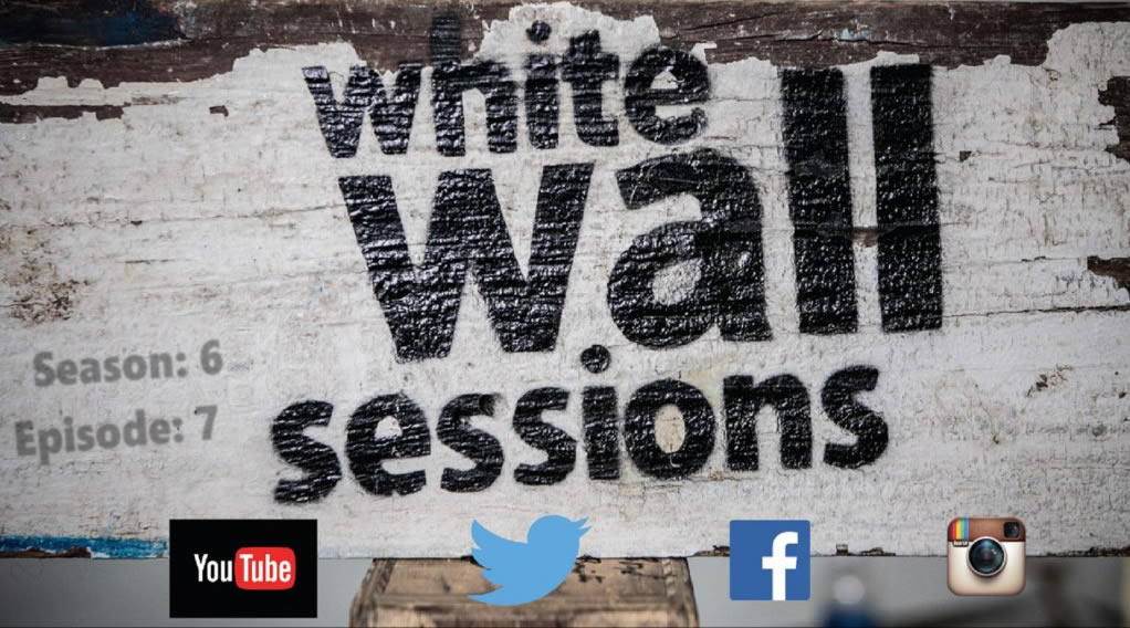 A weather board spray painted with The White Wall Sessions logo and social media icons