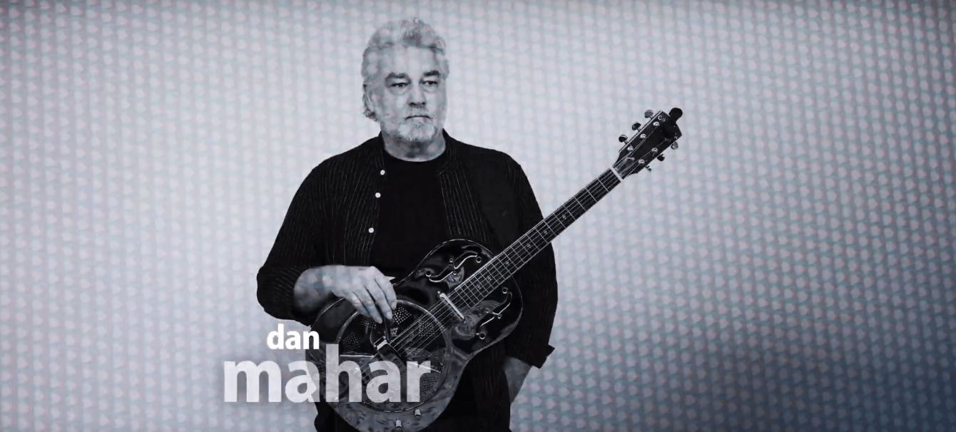 Dan Mahar stands with his resonator looking off into the distance