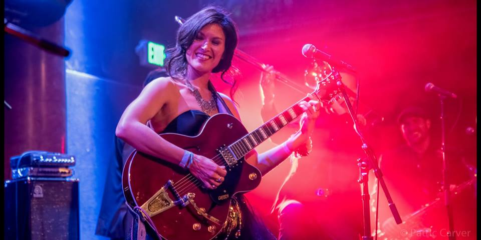 Ellisa Sun plays a hollow body guitar with pink and blue rock n' roll lights