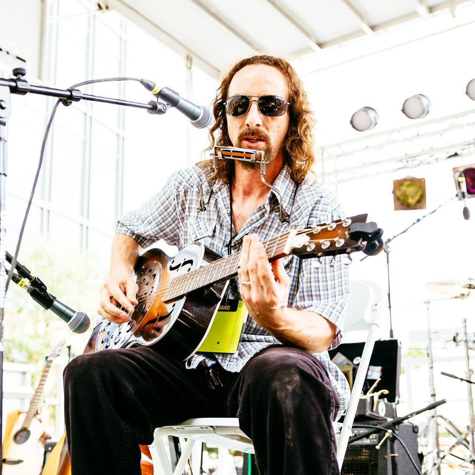 Des Moines' Aaron Earl Short playing slide guitar with sunglasses on