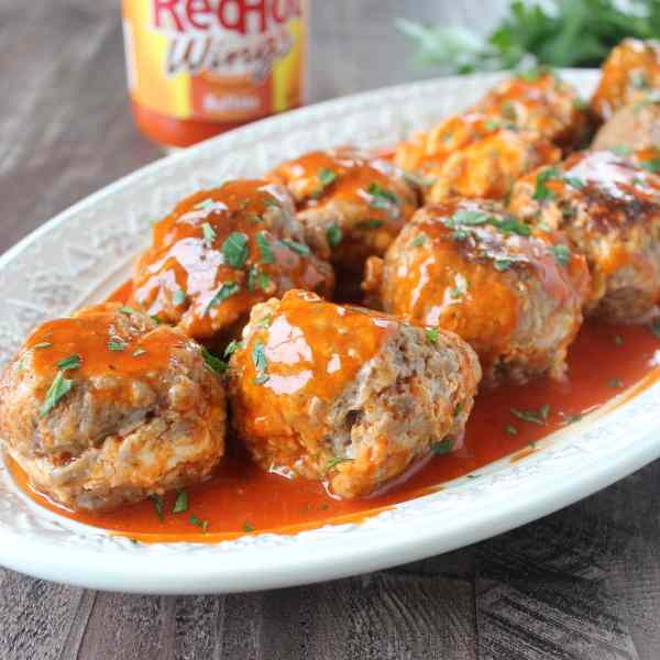 This easy four ingredient recipe for buffalo cheesy slow cooker sausage balls makes the perfect party appetizer for game day, holidays or anytime!