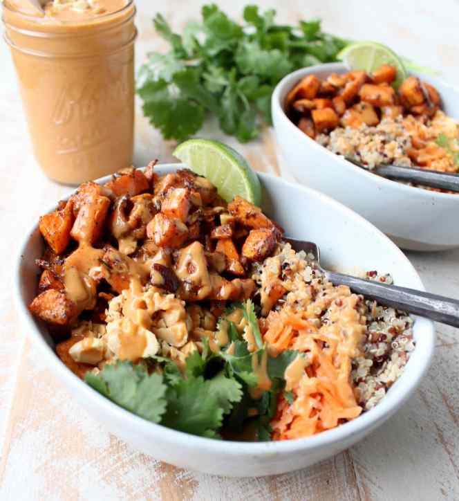 Roasted sweet potatoes and quinoa are topped with delicious Thai peanut sauce in this healthy, gluten free & vegan buddha bowl recipe!