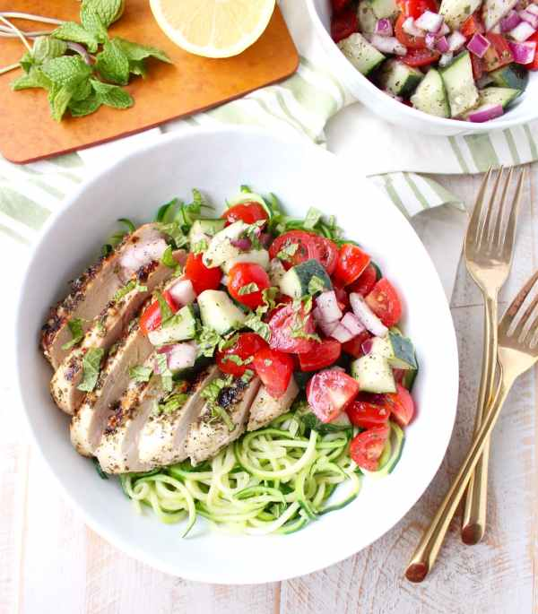 Marinated & grilled Greek Chicken is served on a bowl of zucchini noodles, topped with cucumber tomato salsa for a healthy, gluten free meal made in under 30 minutes!