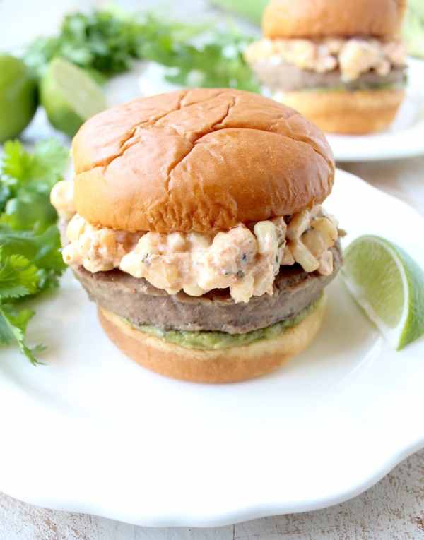 Mexican turkey burgers are covered in cotija cheese, guacamole and grilled Mexican street corn for a flavorful summer burger recipe!