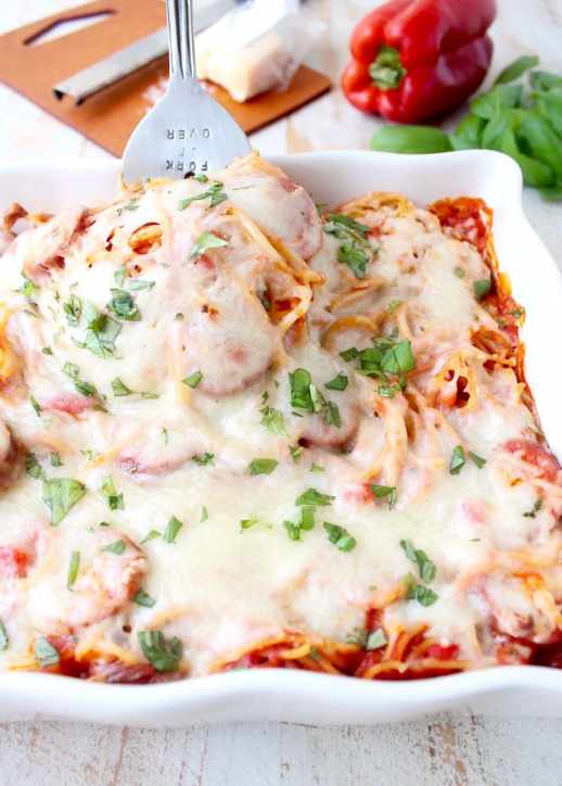 Toss your favorite pizza toppings, like sausage & peppers, with spaghetti & pasta sauce, then top with cheese for an easy pizza baked spaghetti recipe!