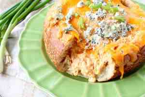 Everyone's favorite buffalo chicken dip is baked right into a bread bowl for the perfect party, game day or weekend appetizer!
