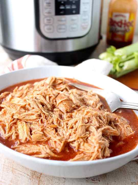 Easily make shredded buffalo chicken for tacos, dips or pasta recipes with this simple Instant Pot Buffalo Chicken recipe!