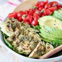 Sliced pesto chicken in bowl with sliced avocado and diced cherry tomatoes