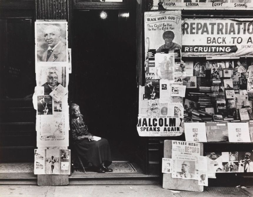 A woman sitting in front of a doorway next to a building covered with posters.