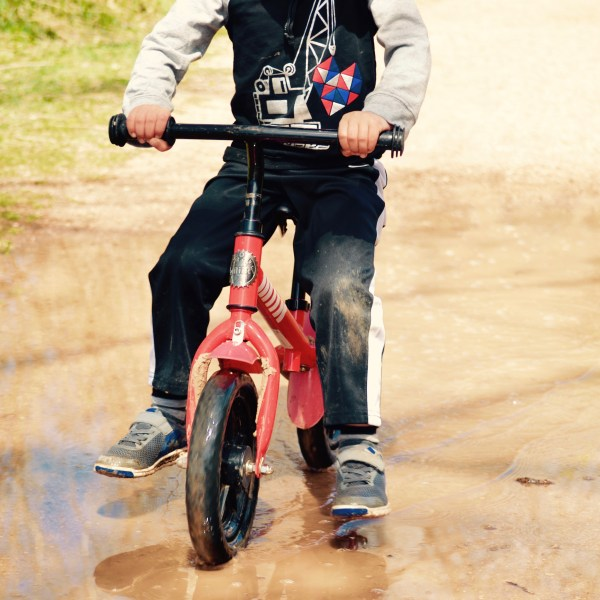 My oldest son when he got too big for the balance bike. Riding it through puddles!
