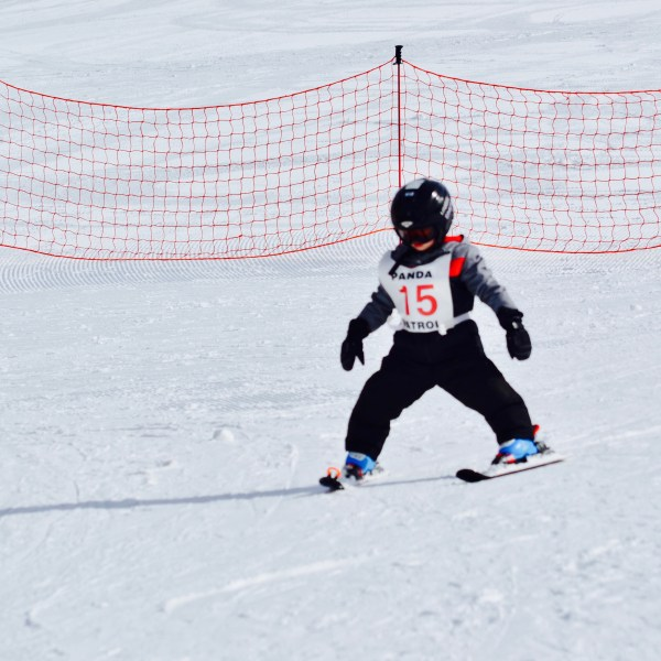 Toddler skiing down a snow covered slope by himself for the first time.