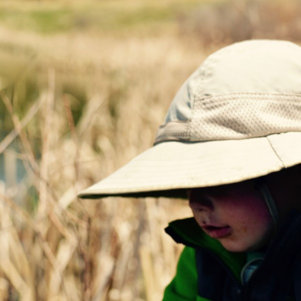 A toddler with a beige sun hat on standing in front of a lake with reeds.