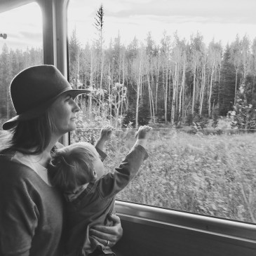 A mom in a hat with her son who is a baby looking out the window of a train to the changing aspens in fall in Colorado.