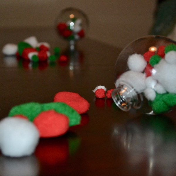 A clear plastic Christmas ornament with red, green, white pom poms on a wooden table.