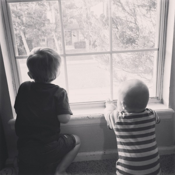 Two little boys looking out a big window. Top 10 ways to boost your mom mood during winter. whitswildtribe.com