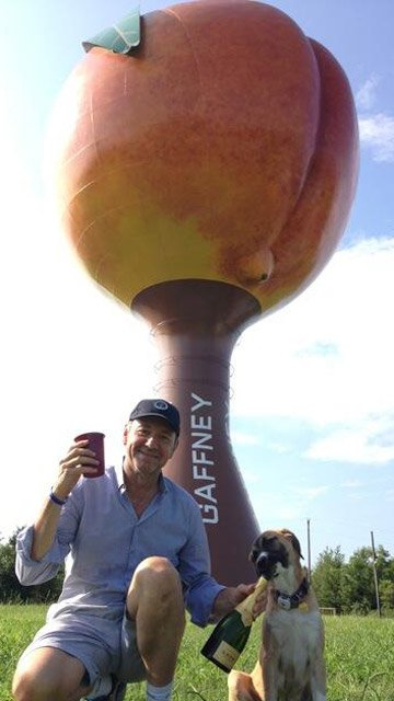 Kevin Spacey posing in front of the Peachoid