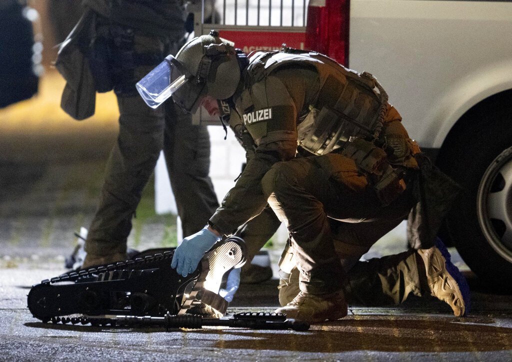 A special forces officer works on a robot in front of a house that is searched through by police in Hanau, Germany Thursday, Feb. 20, 2020. Eight people were killed in shootings in and outside two hookah lounges in a southwestern German city late Wednesday, and authorities were searching for the perpetrators.