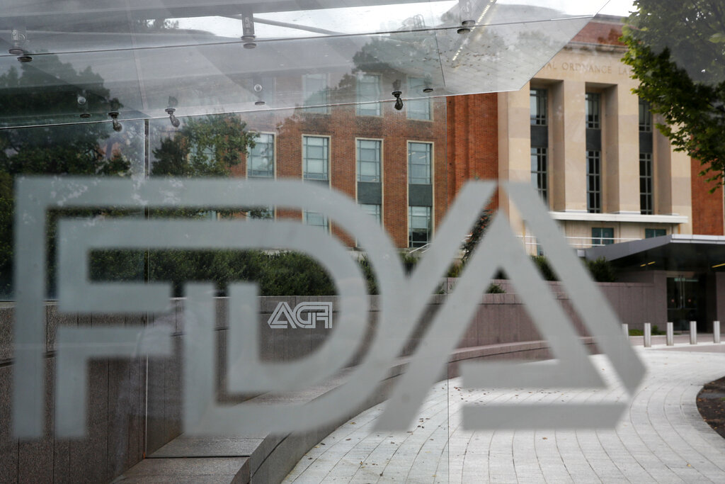 This Aug. 2, 2018, file photo shows the U.S. Food and Drug Administration building behind FDA logos at a bus stop on the agency's campus in Silver Spring, Md. Health officials reported the first U.S. drug shortage tied to the viral outbreak that is disrupting production in China, but they declined to identify the manufacturer or the product. The Food and Drug Administration said late Thursday, Feb. 27, 2020, that the drug's maker contacted health officials recently about the shortage, which it blamed on a manufacturing issue with the medicine's key ingredient.